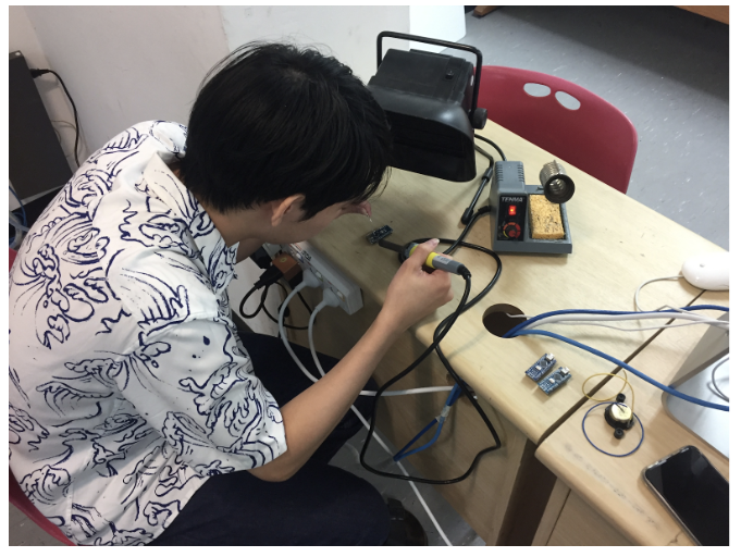 A team member soldering pin headers to an Arduino Nano